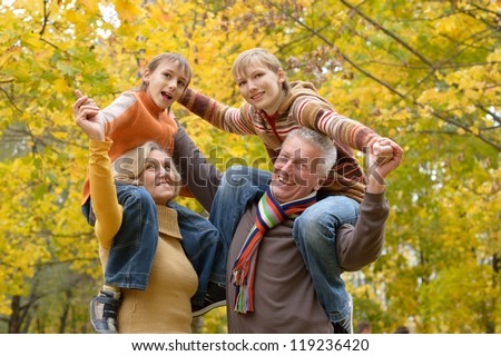 portrait of happy beautiful elderly couple and grandchildren rest fall - stock photo