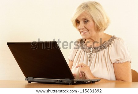 portrait of happy beautiful old woman with a laptop on a beige background