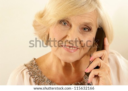 portrait of happy beautiful old woman with a phone on a beige