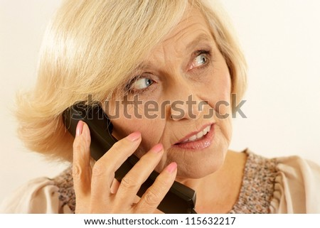 portrait of happy beautiful old woman with a phone on a beige background