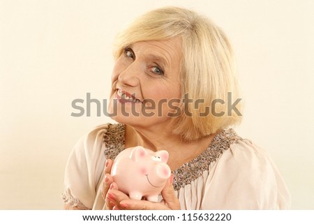 portrait of happy beautiful old woman with piggy bank on a beige
