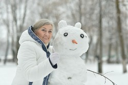 Portrait of happy beautiful senior woman posing in snowy winter park with snowman