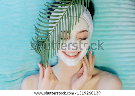 Portrait of happy beautiful woman holds green tropical leaf. Young girl enjoys cream facial mask. Natural cosmetics, skincare, wellness, beauty clinic, facial treatment, cosmetology concept.