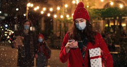 Portrait of happy beautiful young woman in mask typing on smartphone while walking in crowded city on snowy street. Joyful female with christmas gift texting on cellphone outdoors. Holidays concept