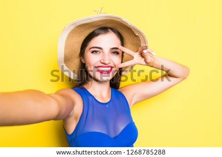 Portrait of happy beautiful young woman taking selfie on her phone and smiling, wearing swimsuit in straw hat isolated on yellow background