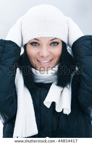 Portrait of happy beautiful young woman with white cap and gloves