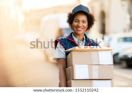 Portrait of happy black courier delivering packages and looking at the camera.  Stockfoto ©