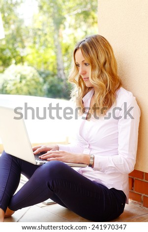 Portrait of happy blogger writing her blog at laptop while sitting at garden at home.