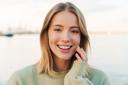 Portrait of happy blonde woman smiling and looking at camera while walking outdoors