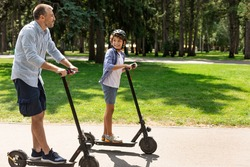 Portrait of happy boy in protective helmet having ride on motorized kick scooter with smiling father at park, spending time together with family on father's day outside, having fun, free copy space
