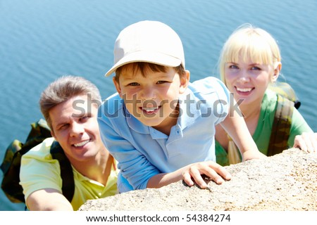 Portrait of happy boy looking at camera with his parents on background