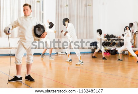 Portrait of happy boy wearing fencing uniform standing in gym with foil and mask in hands