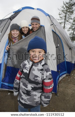 Portrait of happy boy with family peeking heads out of camping tent in background