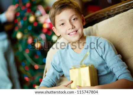 Portrait of happy boy with gift looking at camera