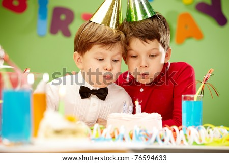 Portrait of happy boys on birthday party blowing at candles on cake - stock photo