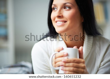 Portrait of happy brunette with mug in hands