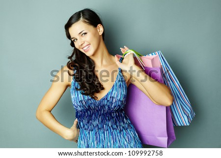 Portrait of happy brunette with paperbags looking at camera with smile