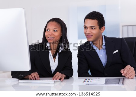 Portrait Of Happy Business People Sitting At The Desk - stock photo