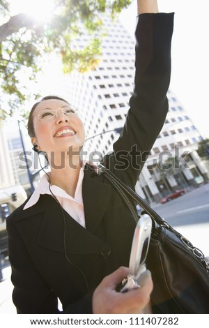 Portrait of happy business woman waving hand with building in the background