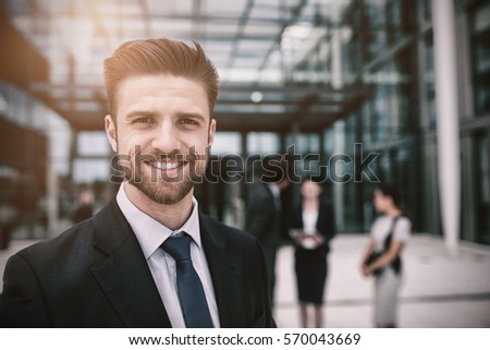 Portrait of happy businessman in office premises #570043669