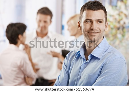 Portrait of happy businessman in office, smiling. Colleagues talking in the background.