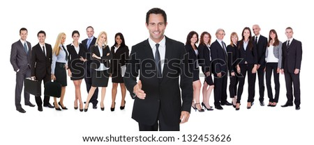 Portrait of happy businessman offering handshake and his team. Isolated on white