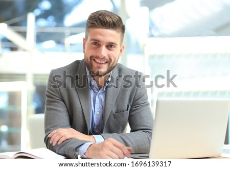 Portrait of happy businessman sitting at office desk, looking at camera, smiling.