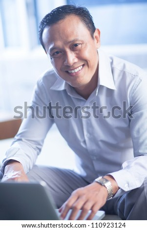 Portrait of happy businessman sitting with laptop and looking at camera