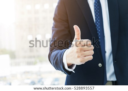 Portrait of happy businessman smiles and showing thumb up sign in office