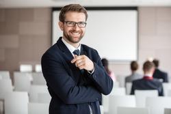 Portrait of happy businessman standing in seminar hall