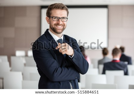 Portrait of happy businessman standing in seminar hall