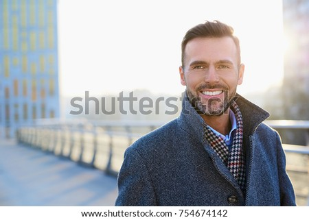 Portrait of happy businessman standing outdoors during sunny winter day