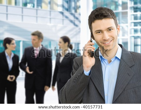 Portrait of happy businessman talking on mobile in office lounge.