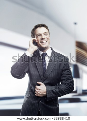 Portrait of happy businessman talking on mobile standing in office, smiling.