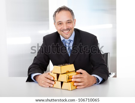 Portrait of happy businessman with golden bars at the office