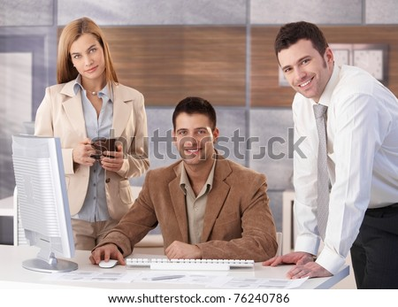 Portrait of happy businessteam working together at desk in office.?