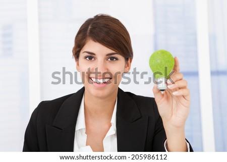 Portrait of happy businesswoman holding green light bulb in office