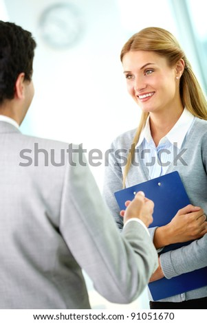 Portrait of happy businesswoman looking at her partner while interacting with him