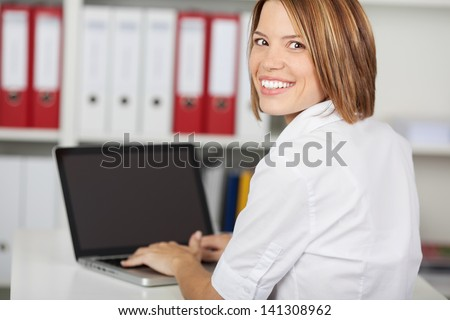 Portrait of happy businesswoman sitting in office with laptop computer, smiling at camera