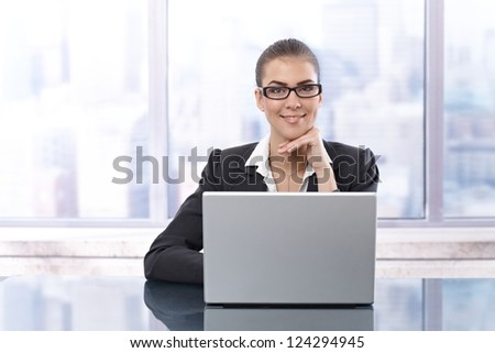 Portrait of happy businesswoman sitting in skyscraper office with laptop computer, smiling at camera.