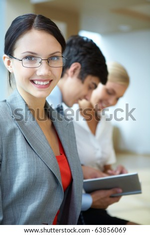 Portrait of happy businesswoman smiling at camera on background of working people - stock photo