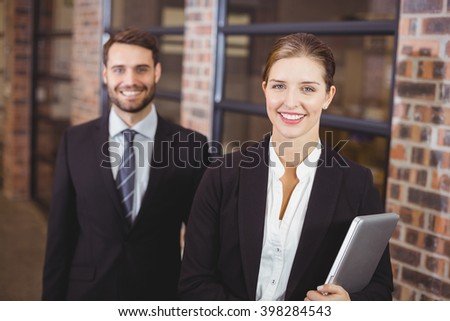 Portrait of happy businesswoman standing with male colleague in office #398284543
