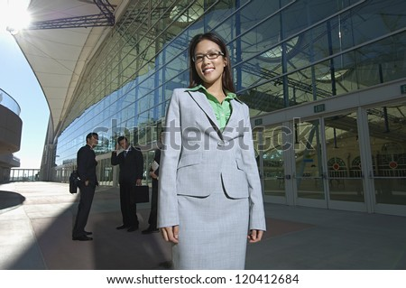 Portrait of happy businesswoman with male colleagues in background outside office