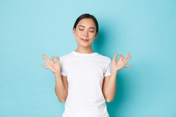 Portrait of happy calm and patient asian woman with closed eyes, smiling pleased, holding hands sideways in lotus pose, reaching nirvana, calm down during meditation, blue background