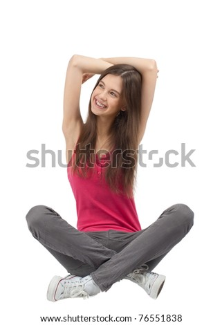 Portrait of happy casual girl sitting and smiling. Over white background