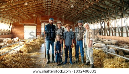 Portrait of happy Caucasian family of three generations standing in shed with livestock and smiling. Old parents with children and grandchildren in stable. Farmers with kids at farm. Foto stock ©