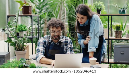 Portrait of happy Caucasian male and female florists flower store owners working and doing inventory. Man typing on laptop at desk in floral shop and talking to woman boss. Business concept Photo stock ©