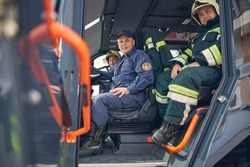 Portrait of happy cheerful driver of big truck with firefighters near him