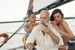 Portrait of happy cheerful old man and girls having fun on sailboat, enjoying each other in romantic summer trip,