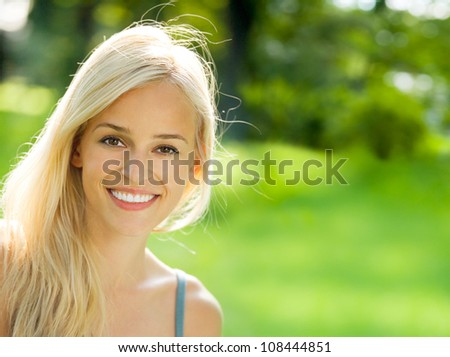 Portrait of happy cheerful smiling young beautiful blond woman outdoors, with copyspace